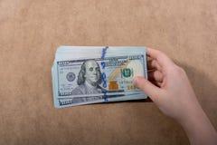 Main tenant le dollar américain sur le fond en bois images libres de droits