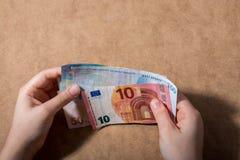 Main tenant le dollar américain sur le fond en bois images stock