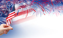 Main tenant le drapeau des Etats-Unis sur le fond de feux d'artifice Photographie stock