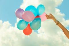 Main tenant le fond de ciel de ballons Photos libres de droits
