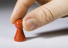 Main tenant le gage rouge sur le fond blanc Image libre de droits