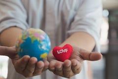 Main tenant le globe et le coeur rouge Aimez le concept de la terre Photos stock