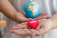 Main tenant le globe et le coeur rouge Aimez le concept de la terre Photo libre de droits
