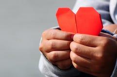 Main tenant le papier rouge de coeur Photographie stock
