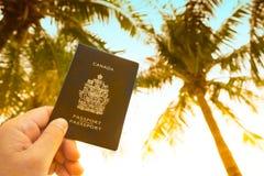 Main tenant le passeport et la carte canadiens photos stock
