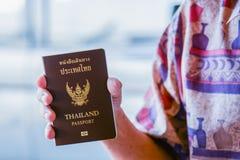 Main tenant le passeport thaïlandais à l'aéroport Photographie stock libre de droits