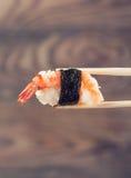 Main tenant le petit pain de sushi utilisant des baguettes Photo libre de droits