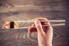 Main tenant le petit pain de sushi utilisant des baguettes Photo stock