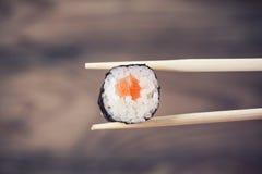 Main tenant le petit pain de sushi utilisant des baguettes Images stock