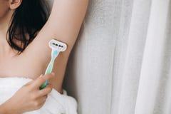 Main tenant le rasoir en plastique et rasant l'aisselle lisse Jeune femme rasant des aisselles avec le plan rapproché en plastiqu photos stock