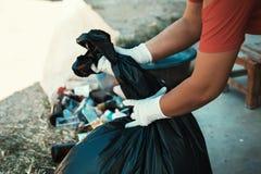 Main tenant le sac de déchets images stock