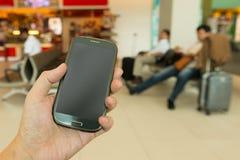 Main tenant le smartphone Photographie stock libre de droits