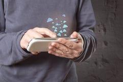 Main tenant le smartphone avec des icônes de nuage Photographie stock libre de droits