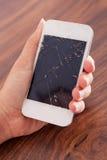 Main tenant le smartphone avec l'écran criqué Photographie stock libre de droits