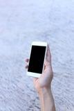 Main tenant le smartphone avec l'écran vide Photographie stock