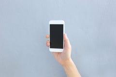 Main tenant le smartphone avec l'écran vide Photographie stock libre de droits