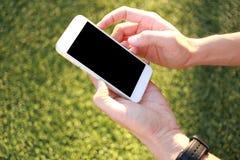 Main tenant le smartphone avec l'écran vide Photos stock