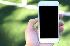 Main tenant le smartphone avec l'écran vide Images stock