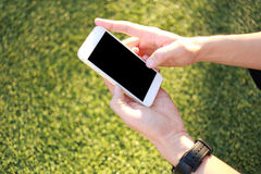 Main tenant le smartphone avec l'écran vide Photo stock