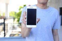 Main tenant le smartphone avec l'écran vide Photos libres de droits