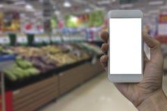 Main tenant le smartphone avec l'écran vide blanc au-dessus de la petite gorgée brouillée Photos stock