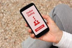 Main tenant le smartphone avec la moquerie en ligne d'application de datation vers le haut d'o Photographie stock libre de droits