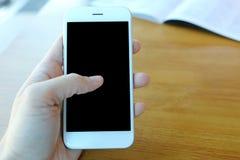 Main tenant le smartphone avec le contact sur l'écran Photos libres de droits
