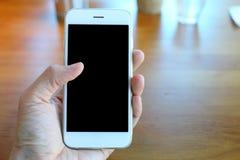 Main tenant le smartphone avec le fond de café Images stock