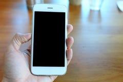 Main tenant le smartphone avec le fond de café Images libres de droits