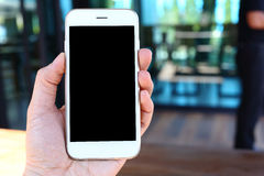 Main tenant le smartphone avec le fond de café Image libre de droits