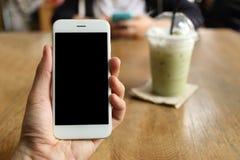 Main tenant le smartphone avec le fond de café de café Image libre de droits