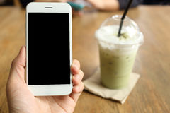 Main tenant le smartphone avec le fond de café de café Photos stock
