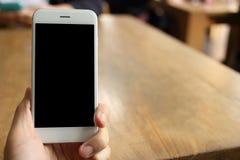 Main tenant le smartphone avec le fond de café de café Image stock