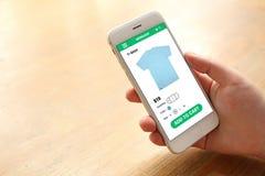 Main tenant le smartphone avec le site Web d'écran de commerce électronique image libre de droits
