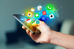 Main tenant le smartphone avec les icônes colorées d'APP Photographie stock