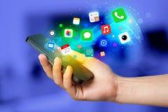 Main tenant le smartphone avec les icônes colorées d'APP Image stock