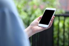 Main tenant le smartphone de maquette avec le fond de bureau Photographie stock libre de droits