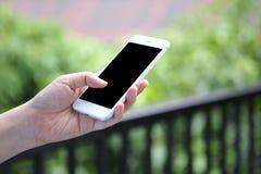 Main tenant le smartphone de maquette avec le fond de bureau Image libre de droits