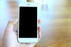 Main tenant le smartphone en café de café Photographie stock libre de droits
