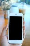 Main tenant le smartphone en café de café Images stock