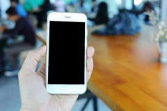 Main tenant le smartphone en café de café Photo libre de droits