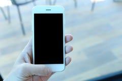 Main tenant le smartphone en café de café Images libres de droits