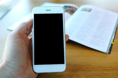 Main tenant le smartphone en café de café Photos stock