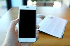 Main tenant le smartphone en café de café Image libre de droits