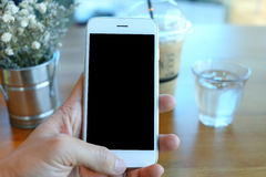 Main tenant le smartphone en café de café Image stock