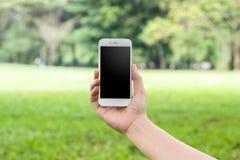 Main tenant le téléphone blanc Image libre de droits