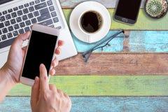 Main tenant le téléphone et l'ordinateur portable intelligents Photo libre de droits