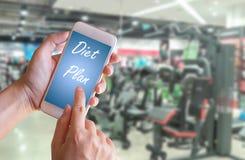 Main tenant le téléphone intelligent avec le plan de régime images stock