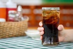 Main tenant le verre de la boisson de kola sur la table Images stock