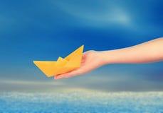 Main tenant un bateau de papier photographie stock libre de droits